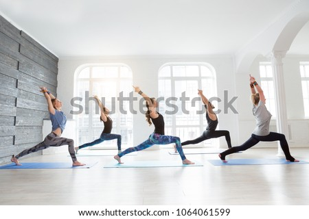 Group of people doing yoga warrior pose at white studio with gesture of will. Fitness class, sport and healthy lifestyle concept