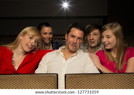 Group of people enjoying themselves in a cinema or movie theater