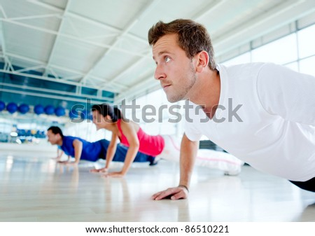 Group of people exercising at the gym doing push ups