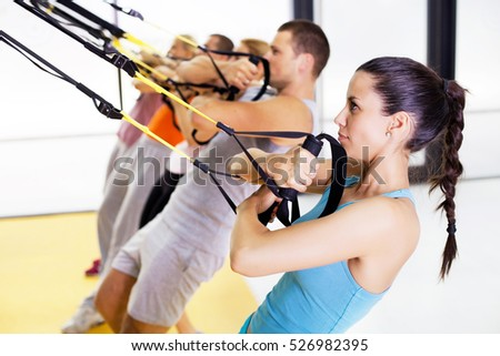 Group of people exercising with hanging fitness straps at the gym.