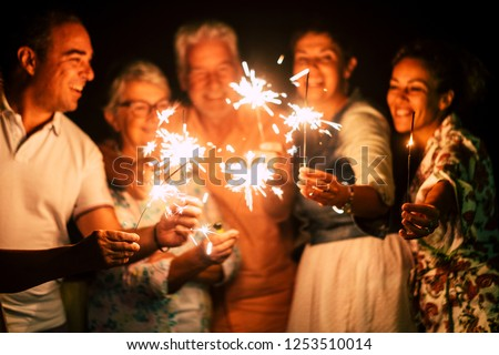 group of people have fun celebrating together new year eve or birthday with sparkles light and fireworks in friendship outdoor at evening time - family and friends different ages celebrate friendly  #1253510014
