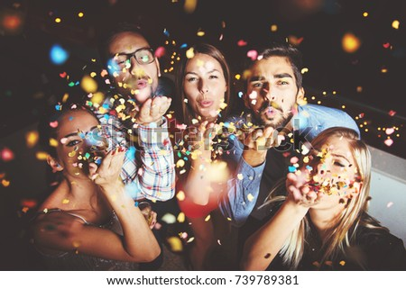 Group of people having a party, blowing confetti  #739789381