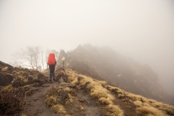 Group of people hikers walking in white fog mountains top above clouds and precipice