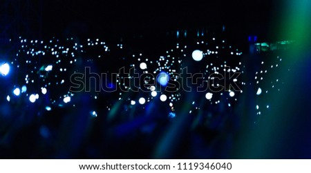 Group of people holding cigarette lighters and mobile phones at a concert crowd of people silhouettes with their hands up. Dark background, smoke, spotlights. Bright lights #1119346040