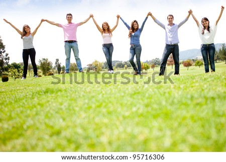 Group of people holding hands at the park and smiling