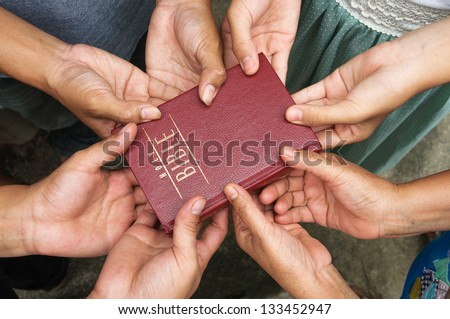Group of people holding Holy Bible and praying.