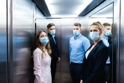 Group Of People In Elevator Wearing Face Masks
