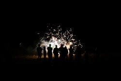 Group of people in silhouette watch fireworks explode on beach in total darkness.