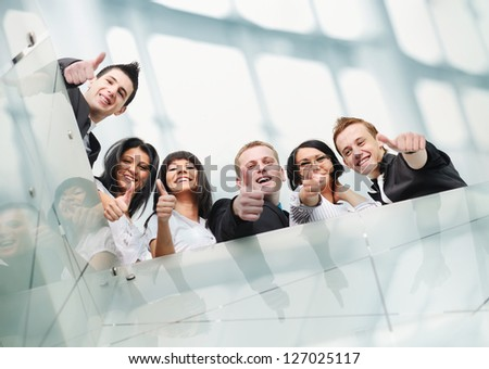 Group of people inside the modern building with thumbs up
