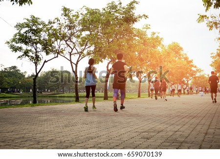 Group of people jogging in the park in the morning #659070139