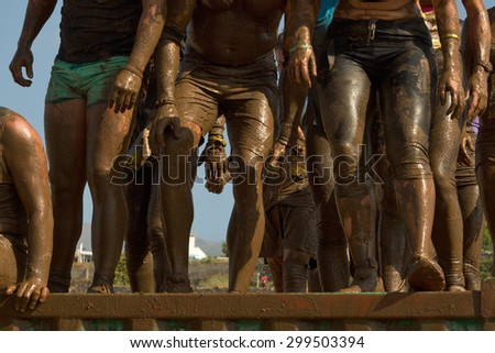 Group of people jumping over an obstacle during the Inferno run mud race