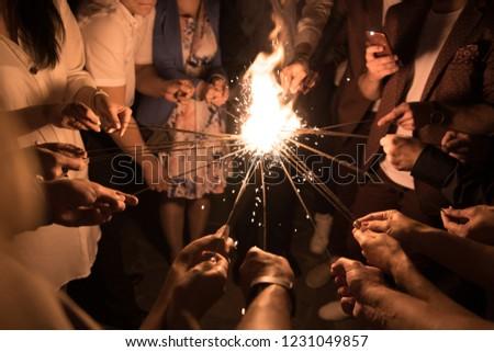 Group of people lighting Bengal lights together. Togetherness. #1231049857