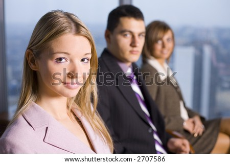 Group of People Looking at the Camera. Focus on first person's face. There's Big Window With Big City View Behind Them.