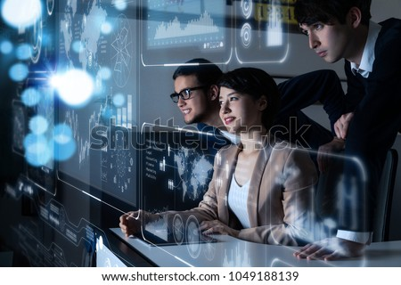 Group of people looking at the futuristic user interface. #1049188139