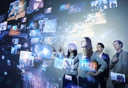 Group of people looking stereoscopic display.
