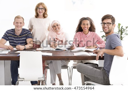 Group of people of different nationalities during language course with mature teacher