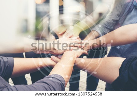 Group of People of Different NATIONALITIES, Putting H่AND Togetherness TEAMWORK or Handshake is Alliance Community Connection, BUSINESS PARTNER. TEAM Stacked With Graphic Connected Networks.