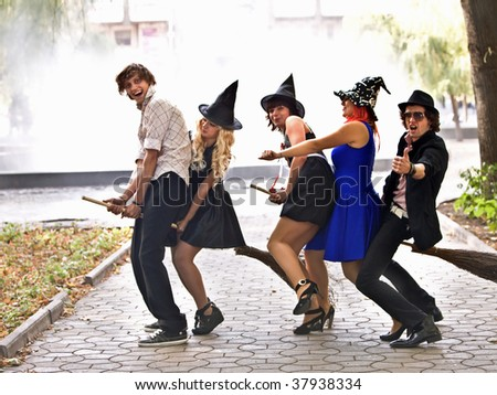 Group of people on broom and halloween witch costume in outdoor.