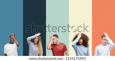 Group of people over vintage colors background surprised with hand on head for mistake, remember error. Forgot, bad memory concept. ストックフォト ©