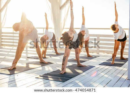 group of people practicing yoga on the seaside during the sunrise