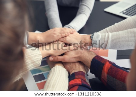 Group of people putting hands together as symbol of unity in office #1311210506