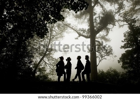Group of people silhouette in the misty forest.
