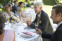 Group of people sitting at wedding tables in garden
