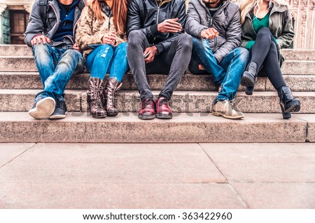 Group of people sitting on a staircase outdoors, close up on low section body - Multiracial friends talking and having fun on a meeting outdoors