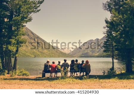 Group of people sitting on a wooden bench admiring the view of the mountains and the lake