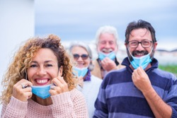 group of people smiling and looking at the camera taking off their medical and surgical mask after coronavirus and quarantine concept - covid 19 pandemic lifestyle wearing mask