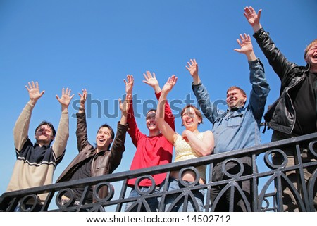 group of people stand with  hands lifted in  greeting