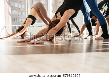 Group of people standing and doing yoga exercises barefoot in studio