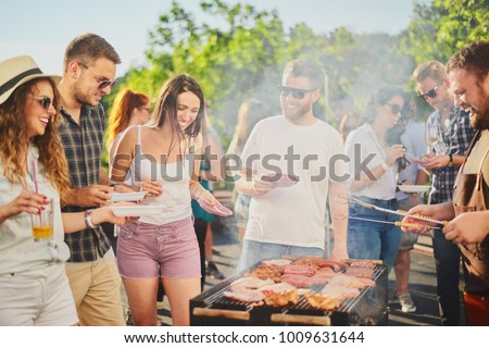 Photo of  Group of people standing around grill, chatting, drinking and eating.