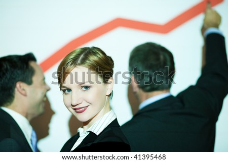 Group of people standing in front of business graph projected on wall (people illuminated by projector , there are wirelines from projection on people and screen, selective focus on girl in front)