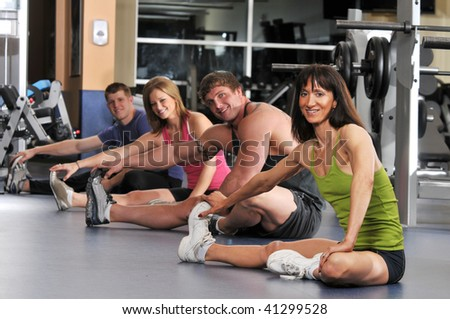 Group of people stretching at the gym with focus on the trainer on the foreground