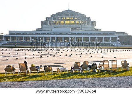 Group of people sunbathing at Centennial Hall, Wroclaw, Poland