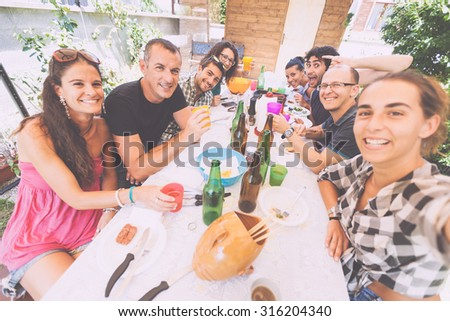 Group of people taking selfie while having lunch outdoor. A multicultural group of friends is taking a selfie while eating. They are happy and there are a lot of plates and bottles on the table.