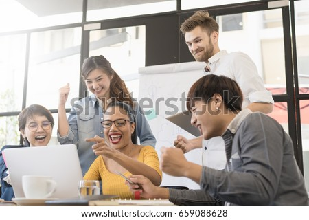 Group of people various nationality glad and cheerful for success them work with laptop at modern office. Feeling happy and enjoy with achievement project