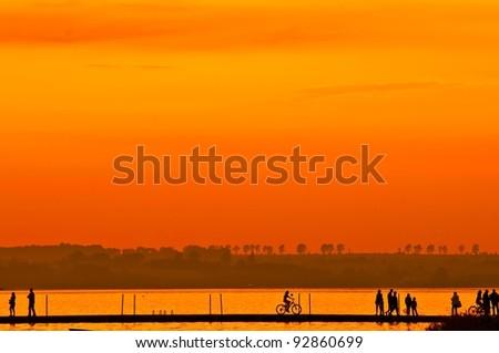 Group of people walking and biking on boardwalk at sunset