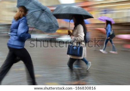 Group of people walking down the street in rainy day  in motion blur - Shutterstock ID 186830816