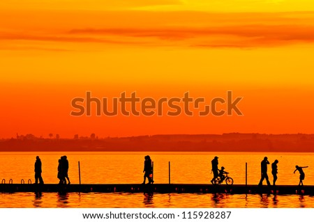Group of people walking on boardwalk at sunset