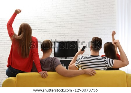 Group of people watching TV together on sofa in living room. Space for text