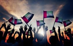 Group of People Waving Flag of UAE in Back Lit