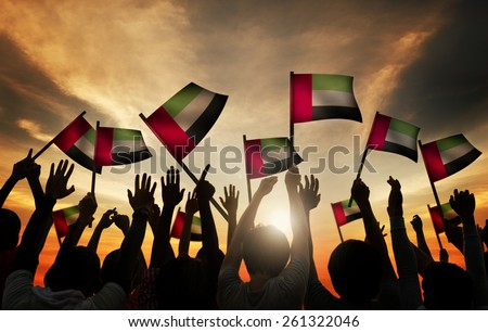 Group of People Waving Flag of UAE in Back Lit