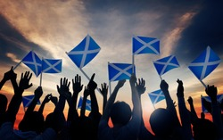 Group of People Waving Scottish Flags in Back Lit