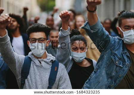 Group of people wearing face mask protesting and giving slogans in a rally. Group of demonstrators protesting in the city. Foto stock ©