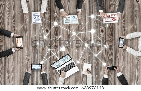 Group of people with devices in hands working together as symbol of networking and communication #638976148