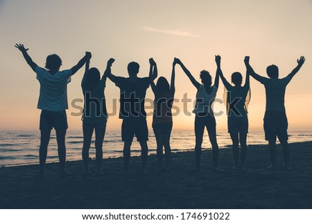 Group of People with Raised Arms looking at Sunset #174691022