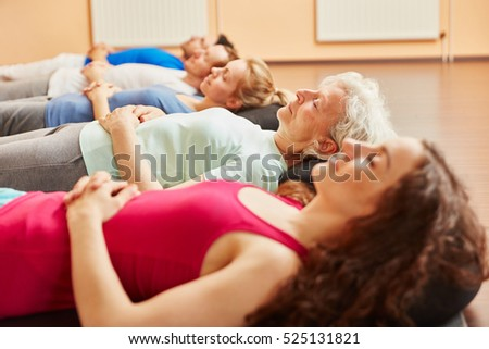 Group of people with senior relaxing  making breathing exercise at yoga class #525131821