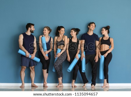 Group of people with yoga mats near color wall #1135094657